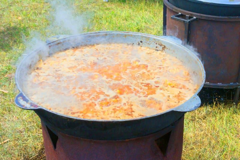 可口乌兹别克人肉饭在自然的一口大锅被烹调在火炉 库存照片