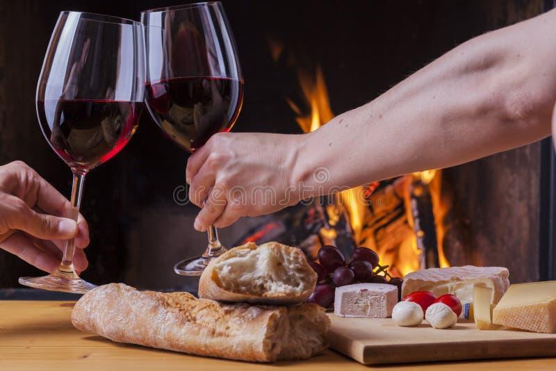 可口乳酪和酒在壁炉 免版税库存图片