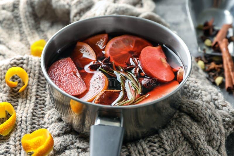 可口加香料的热葡萄酒平底深锅在温暖的格子花呢披肩的 库存图片