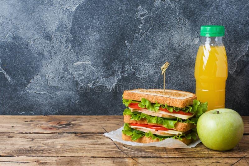 可口和新鲜的三明治、新鲜的苹果计算机和橙汁过去在一张黑暗的木桌上 r 概念学校早餐 免版税库存图片
