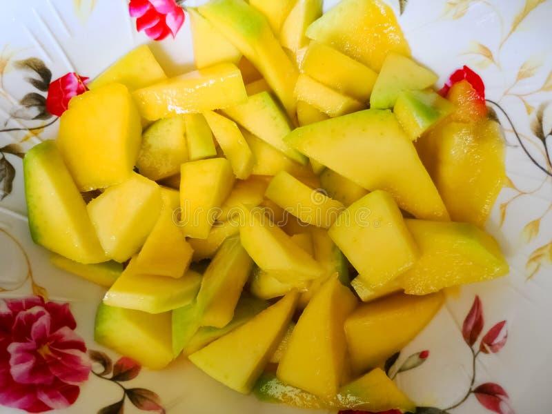 可口和水多的切好的成熟芒果在一块白色板材服务 免版税库存图片