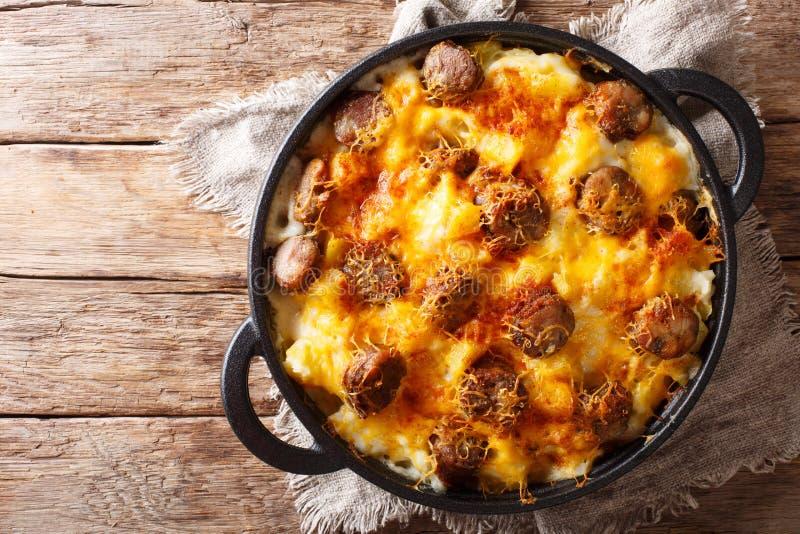 可口土豆砂锅,与乳酪调味料特写镜头的香肠在煎锅 水平的顶视图 库存照片