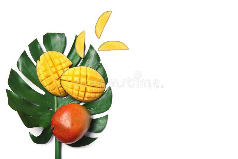 可口在白色,顶视图隔绝的芒果和绿色叶子 免版税图库摄影