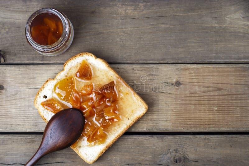 可口多士用甜果酱和匙子在木背景,顶视图,拷贝空间 库存图片