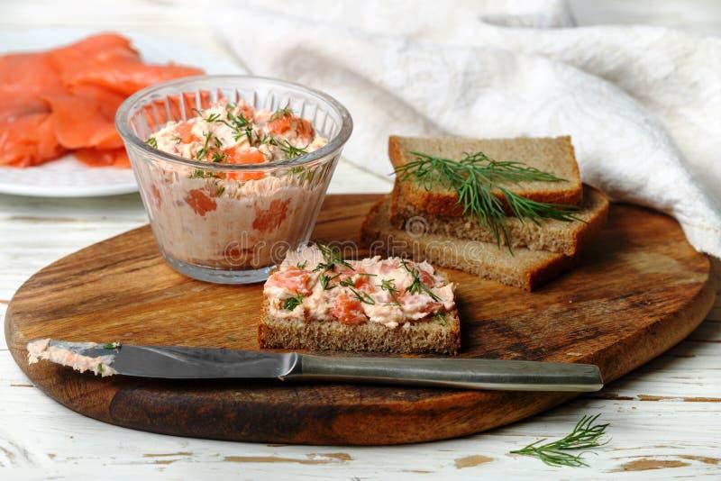 可口奶油甜点、riyet、熏制鲑鱼鳟鱼头脑、垂度,奶油芝士、莳萝和辣根在黑麦面包切片 免版税库存照片