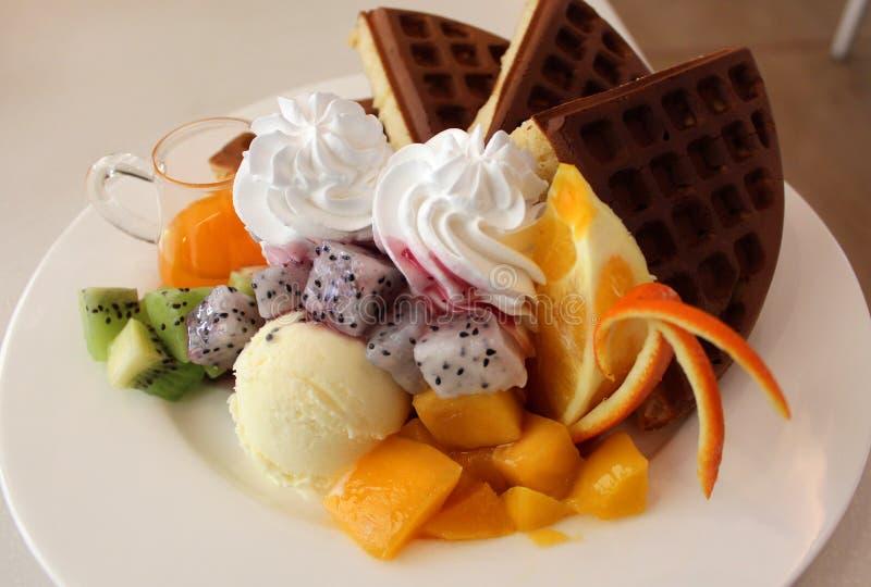 可口奶蛋烘饼板材与冰淇凌、调味汁和新鲜水果的 库存照片