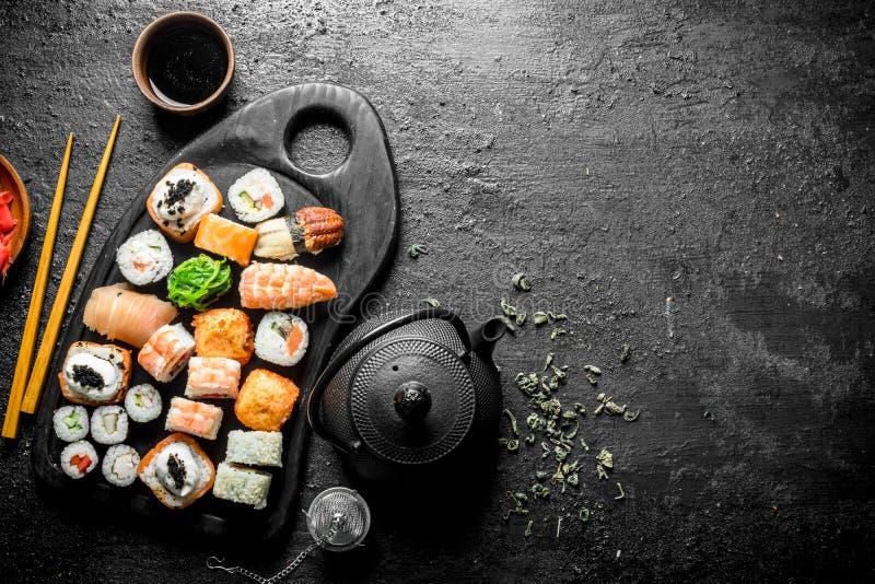 可口寿司卷片断在切板的用在茶壶的茶 库存照片