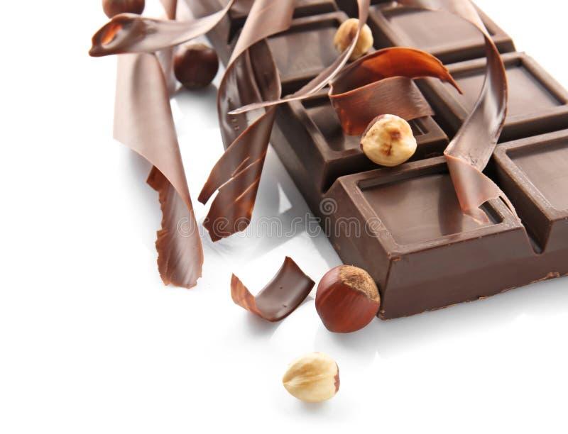 可口巧克力块、削片和榛子在白色背景 库存图片