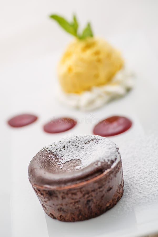 可口巧克力烤饼用果子调味汁和香草冰淇淋在白色板材,巧克力方旦糖 免版税图库摄影