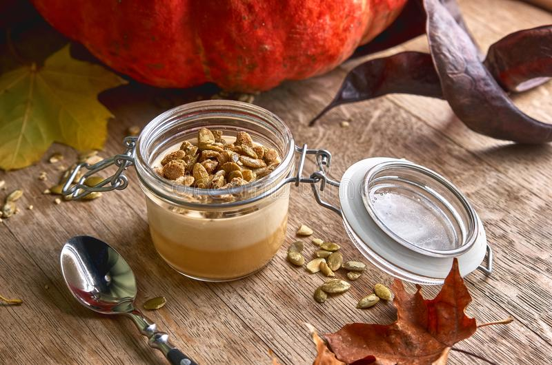 可口意大利点心panna陶砖用南瓜和焦糖调味,在木背景的新鲜的南瓜籽 免版税库存图片