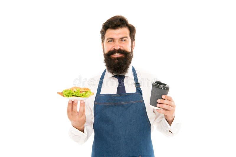 ( 可口新月形面包 人有胡子的侍者穿戴围裙运载板材用食物和咖啡杯 咖啡馆食物 免版税图库摄影