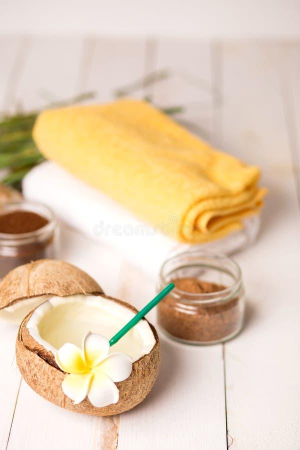 可口新鲜的椰子在木背景的汁和秸杆特写镜头与白花的与毛巾和巧克力身体洗刷 免版税库存图片