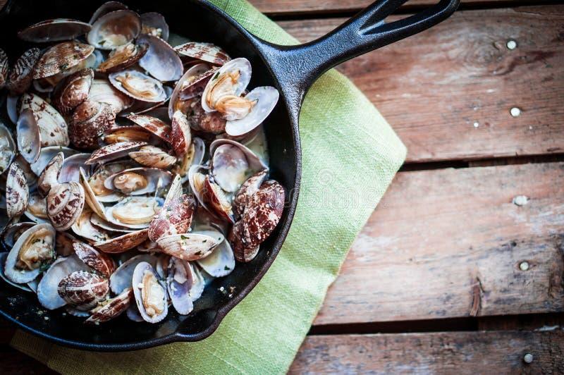 可口新鲜的汽锅蛤蜊生铁长柄浅锅用大蒜a 免版税图库摄影