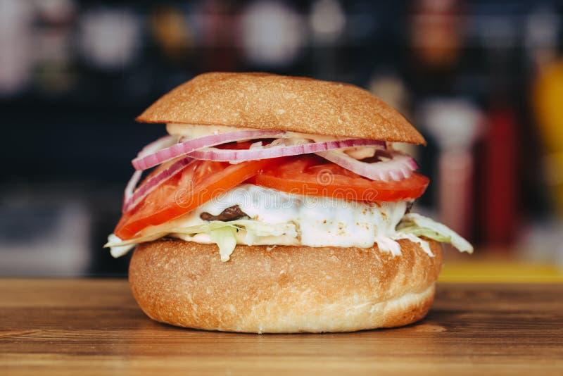 可口新鲜的自创芝士汉堡用烤肉、乳酪、蕃茄、莴苣和洋葱圈在牛皮纸 街道食物 免版税库存图片