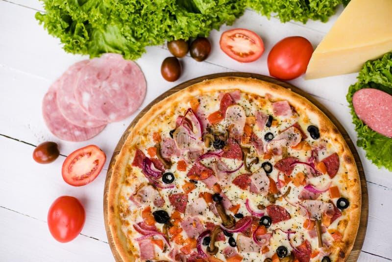 可口新鲜的薄饼用在白色木桌上的蕃茄、mashrooms、烟肉和乳酪无盐干酪 顶视图 免版税库存照片