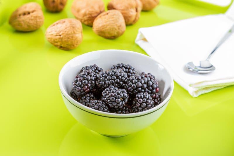 可口新鲜的黑莓和成熟黑和带红色石榴石 在绿色和白色背景的白色碗 用杏子,柠檬 库存照片
