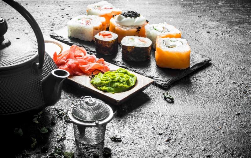 可口日本寿司卷片断用绿茶和调味汁 免版税库存照片