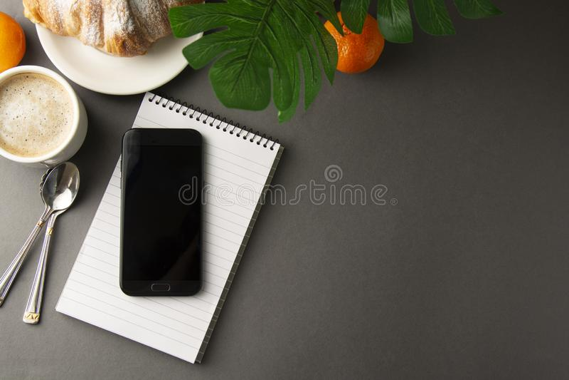 可口早餐咖啡用新月形面包和柑橘水果 心形的配件箱 与智能手机的工作表 法式酥皮点心和杯子 图库摄影