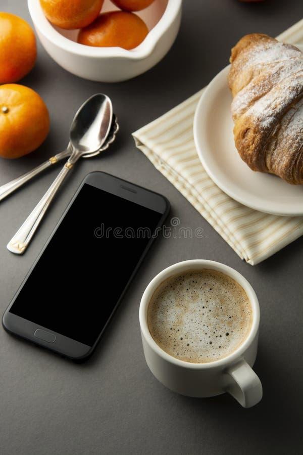 可口早餐咖啡用新月形面包和柑橘水果 心形的配件箱 与智能手机的工作表 法式酥皮点心和杯子 免版税库存图片