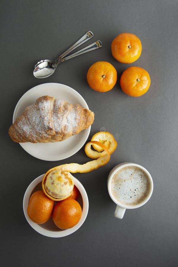 可口早餐咖啡用新月形面包和柑橘水果-桔子 早晨咖啡因 法国,新鲜的酥皮点心和咖啡或 免版税库存照片