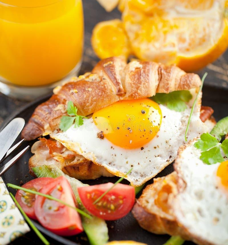 可口早餐用与荷包蛋的新月形面包三明治 库存照片