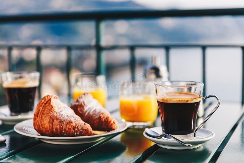可口早餐用咖啡、酥皮点心和橙汁过去在阳台服务有海视图 图库摄影