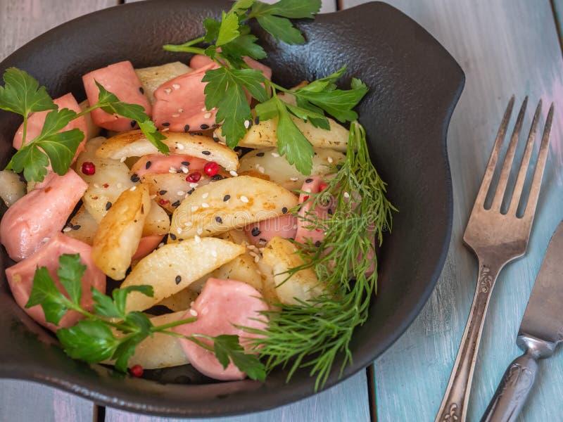 可口早餐用在一个黑色的盘子和香肠油煎的土豆用在委员会盘子、利器、叉子和刀子的辣草本, 库存图片
