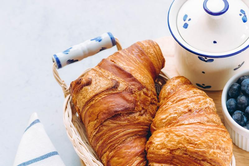 可口早餐用新鲜的新月形面包和蓝莓在轻的背景,明亮的新心情 免版税图库摄影