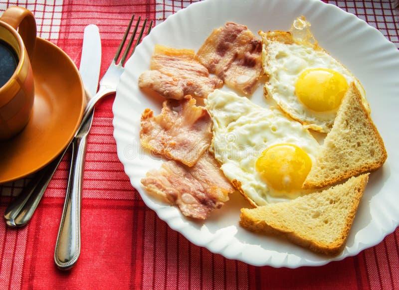 可口早餐-一杯咖啡,荷包蛋,烟肉和多士板材,在利器旁边在红色方格的餐巾 库存图片