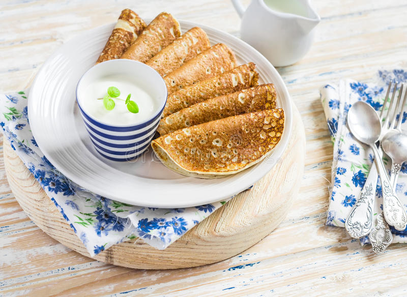 可口早餐-薄煎饼和奶油在一块陶瓷板材在轻的木背景 免版税库存照片