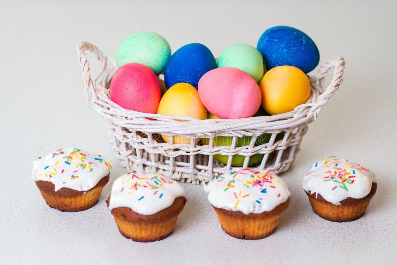 可口杯形蛋糕和被绘的鸡蛋复活节的 免版税库存照片