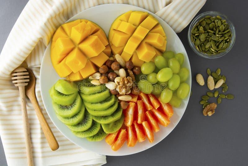 可口果子普拉特隔绝了 芒果,猕猴桃,柑橘,坚果,葡萄 各种各样的异乎寻常的果子的混合 健康水果沙拉,健康 库存图片