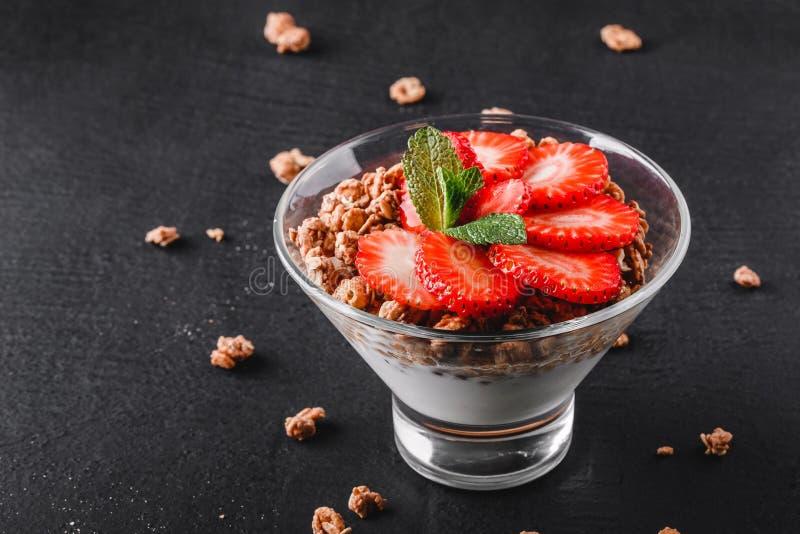 可口格兰诺拉麦片用酸奶和新鲜的草莓在玻璃在黑背景 免版税库存照片