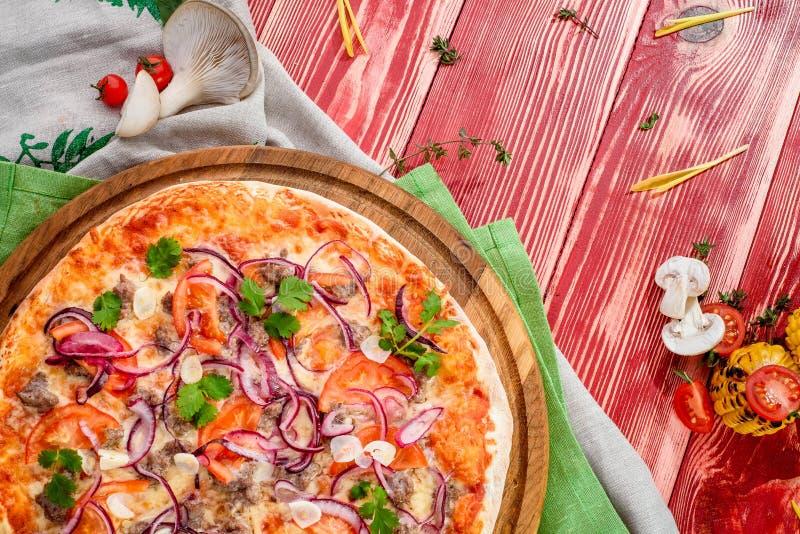 可口比萨用肉、蕃茄、葱、大蒜、荷兰芹和乳酪在红色木背景 免版税图库摄影