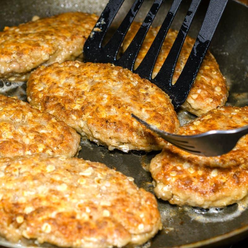 可口水多的自创炸肉排在煎锅被烹调 在 免版税库存照片