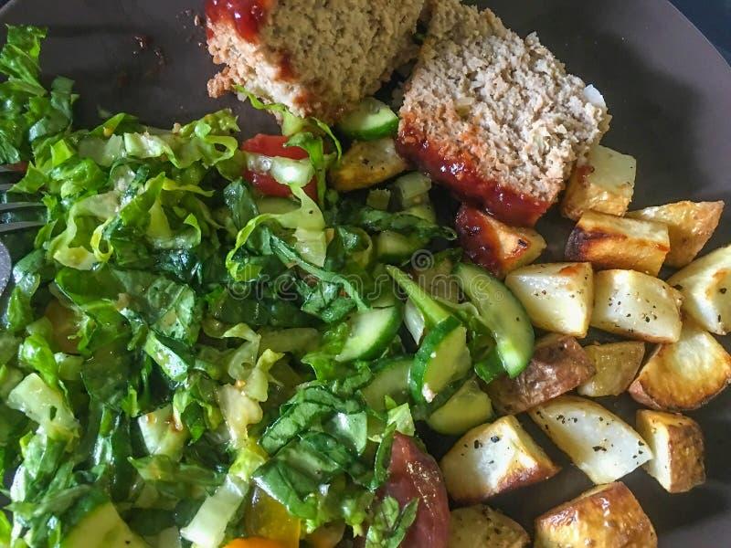 可口油煎的土豆、肉饼和沙拉 免版税图库摄影