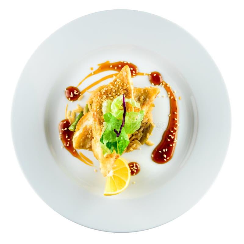 可口油煎的鳕鱼片用意大利煨饭、沙拉和柠檬在wh 库存照片