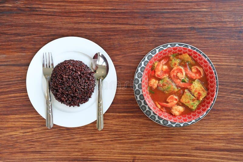 可口泰国黄色咖喱用虾和油煎的草本菜煎蛋卷在碗服务用煮熟的泰国黑茉莉花米莓果 免版税库存照片