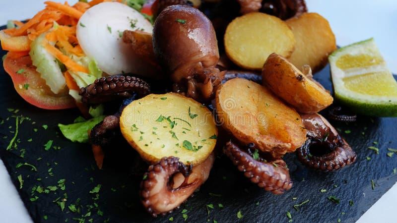 可口海鲜膳食用烤章鱼和被烘烤的土豆和沙拉在一个黑板岩开胃菜板服务 免版税库存图片