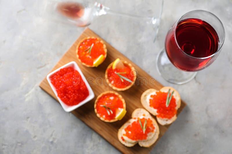 可口点心用红色鱼子酱和杯在灰色桌上的酒 免版税库存照片