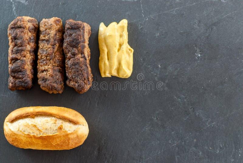 可口烤肉末卷mici ori mititei传统罗马尼亚和巴尔干盘服务与芥末和面包传统 图库摄影