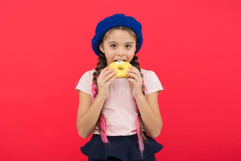 可口甜多福饼 女孩在贝雷帽帽子举行多福饼红色背景中 孩子嬉戏的女孩吃多福饼 香蕉卫生措施营养磁带 库存图片