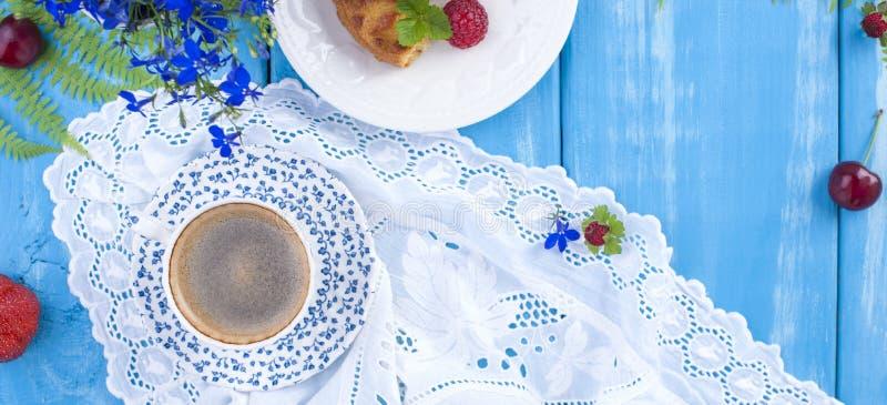 可口甜早餐和芬芳咖啡,在蓝色木背景、花和莓果 长的格式,横幅 复制空间 免版税库存照片