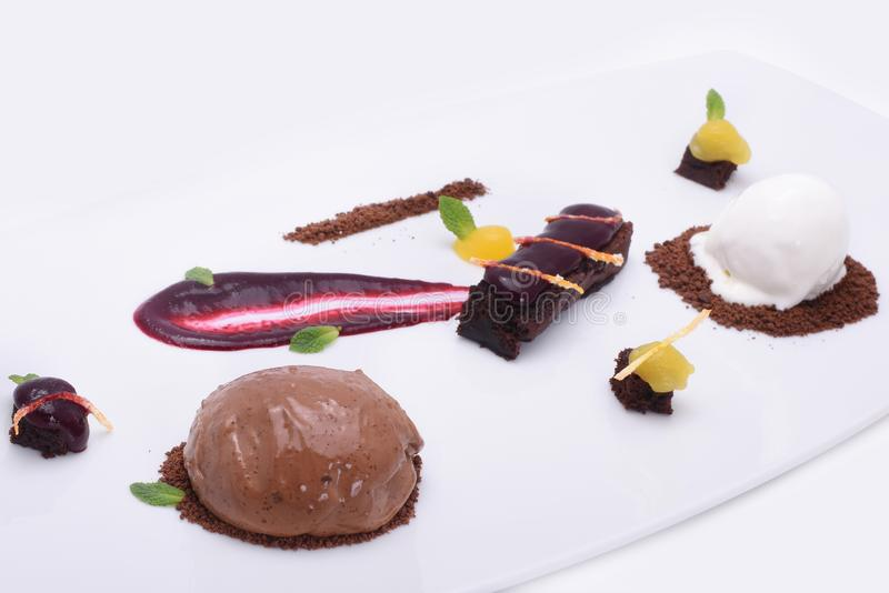 可口甜点-巧克力蛋糕、果子糖果和冰淇淋球在一块白色板材 免版税图库摄影