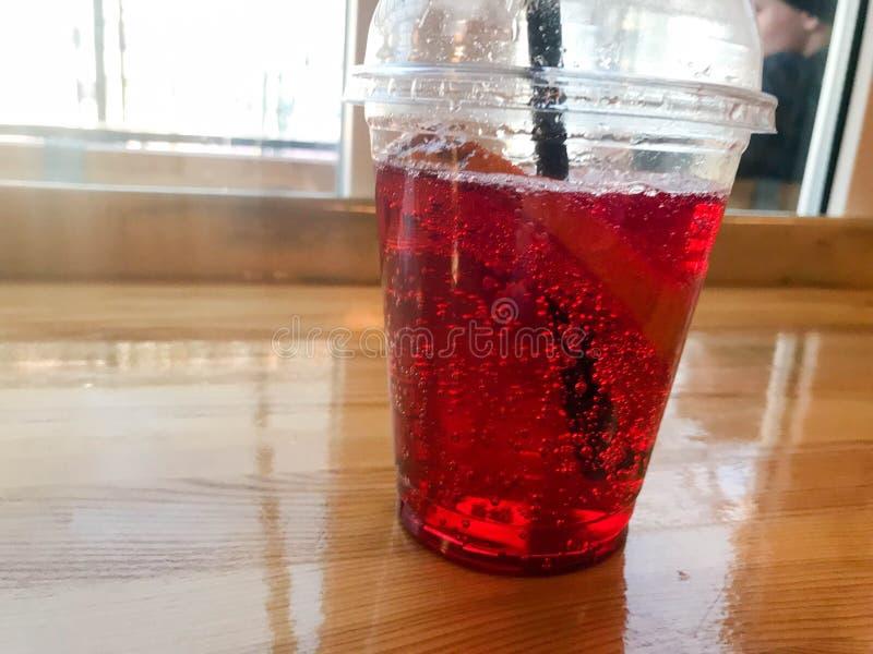 可口甜莓草莓樱桃柠檬水自然用糖浆和气泡在塑料一次性杯子有秸杆的 免版税库存图片