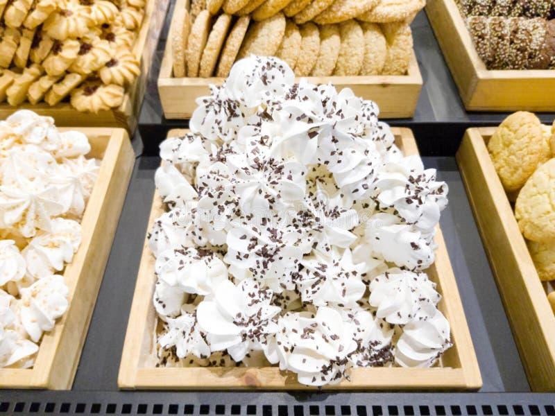可口甜蛋白甜饼和饼干在商店窗口里 免版税库存照片