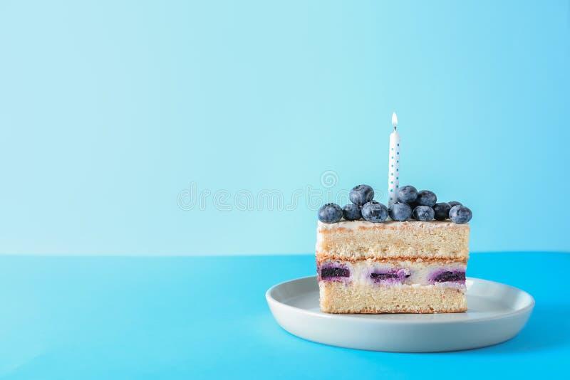 可口生日蛋糕片断与燃烧的蜡烛的在颜色背景 库存照片