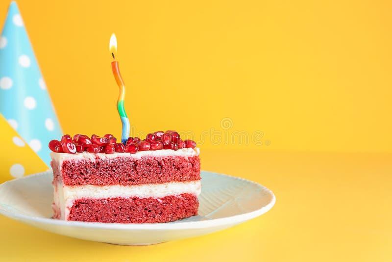 可口生日蛋糕片断与燃烧的蜡烛的在颜色背景 免版税库存图片