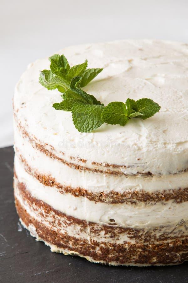 可口白色奶油色浮冰块特写镜头与在黑人委员会服务的薄荷叶的 与奶油的自创赤裸蛋糕,装饰 免版税图库摄影