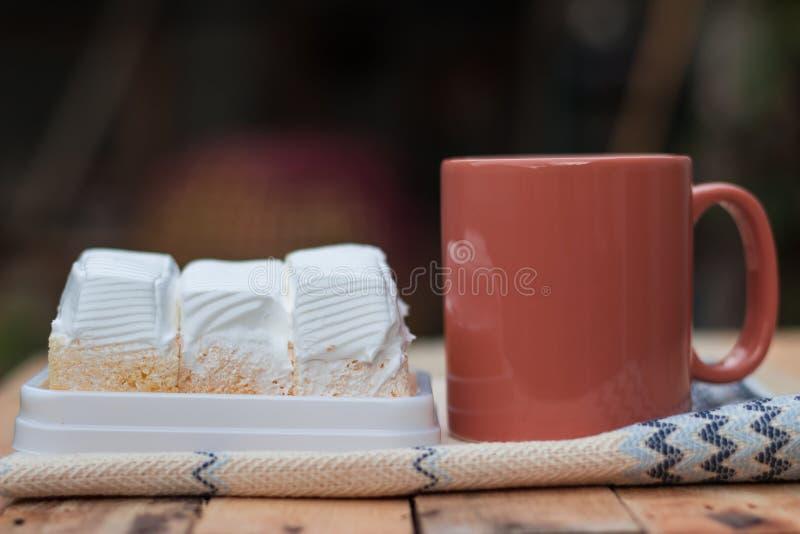 可口白蛋糕和咖啡杯 免版税库存图片